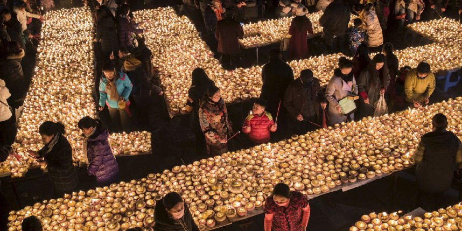 La gente enciende lámparas durante el Festival de la lámpara de la mantequilla en China. Foto:AFP