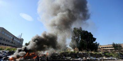 Recicladores de basura empujan su carrito frente a la quema de una pila de desechos en Beirut, Líbano. Foto:AFP