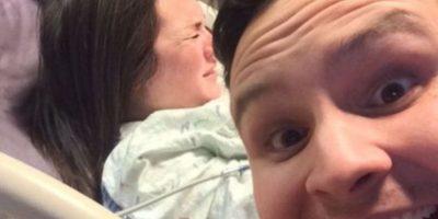 Un hombre posa frente a la cámara con una amplia sonrisa mientras su esposa sufre durante el parto. Foto:Vía Reddit.com