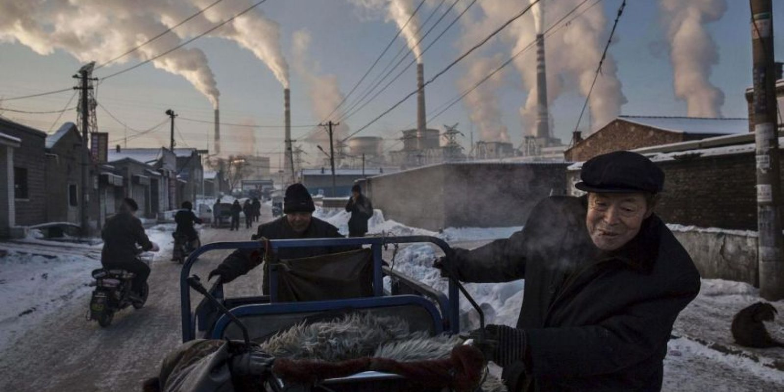 Kevin Frayer. Un anciano chino empuja un triciclo junto a un fábrica en China Foto:worldpressphoto.org