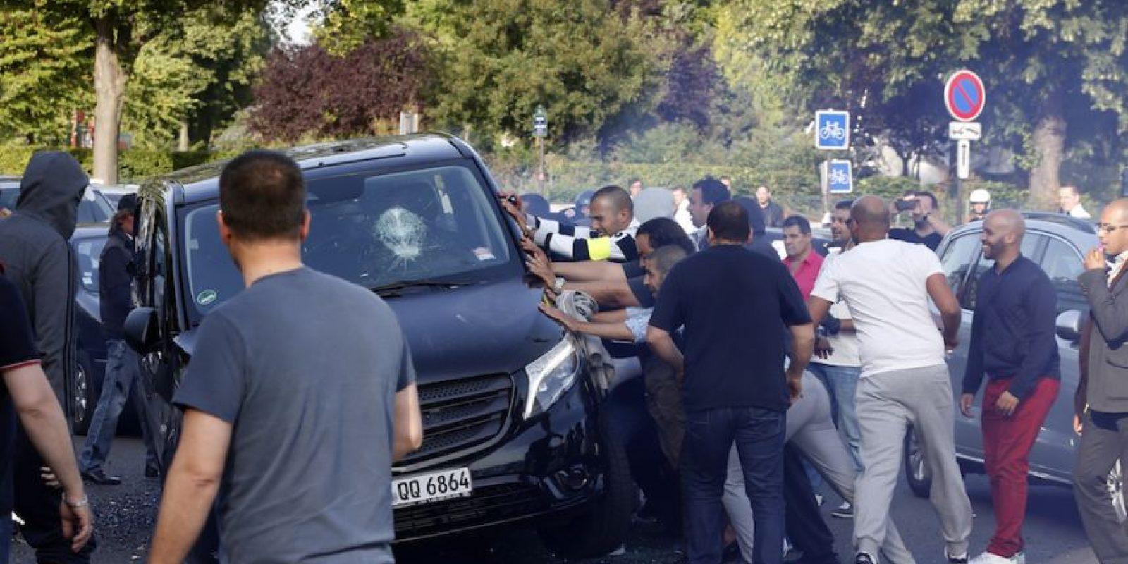 Taxistas tratan de voltear un Uber. Foto:AFP