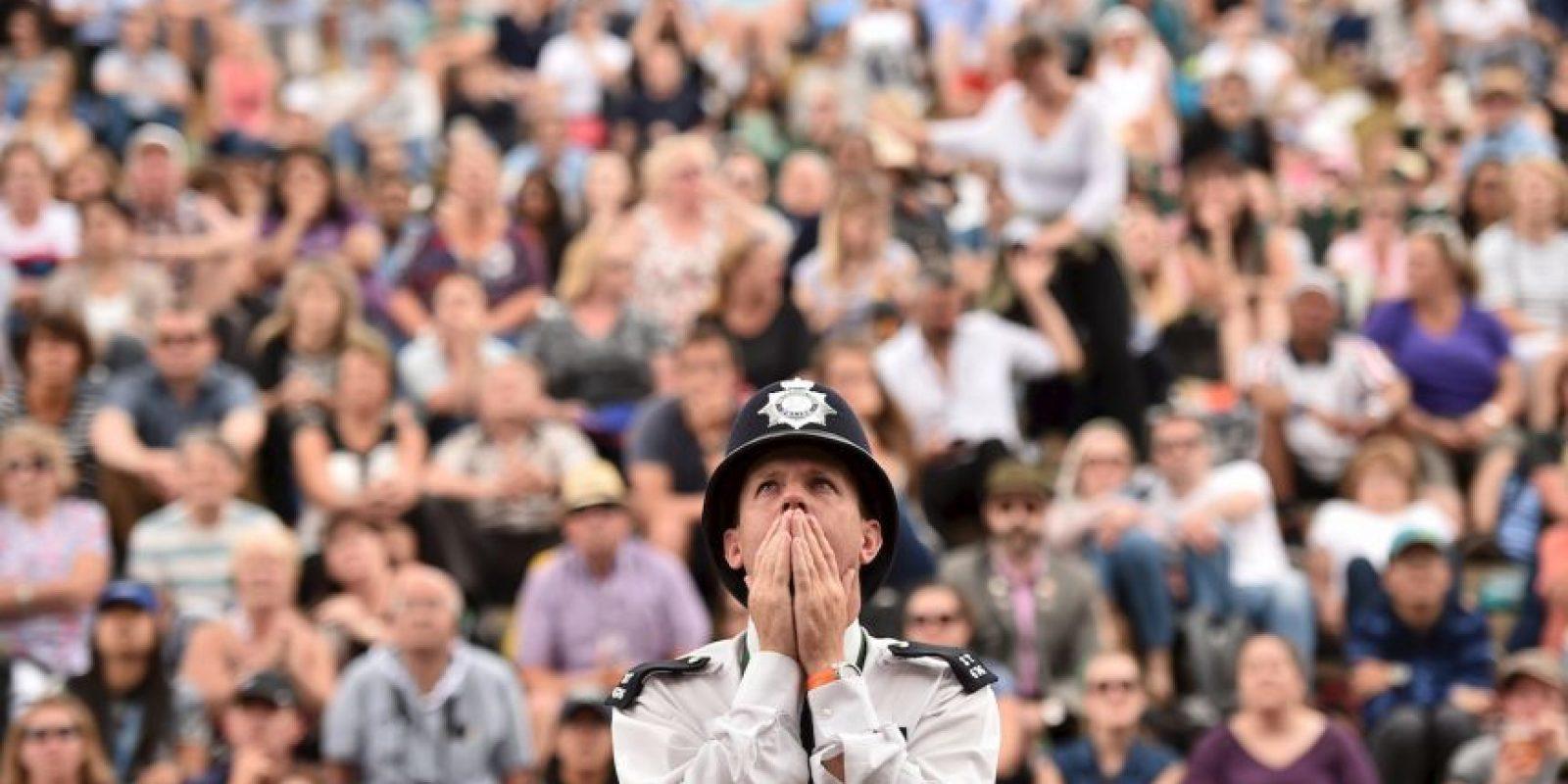 Un oficial de policía británico reacciona cuando ve una pantalla gigante que muestra el Campeonato de Wimbledon. Foto:AFP