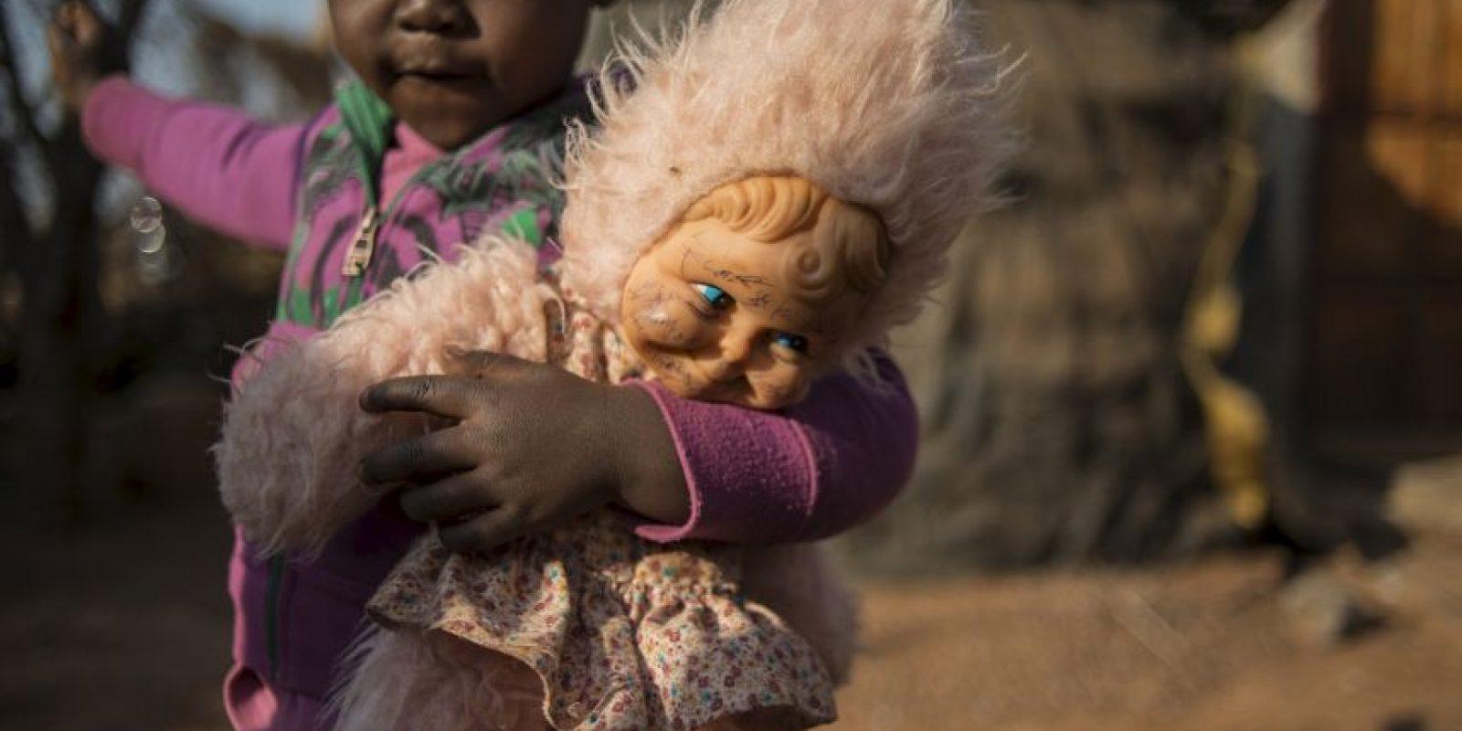 Niña juega con su muñeca en Sudáfrica. Foto:AFP