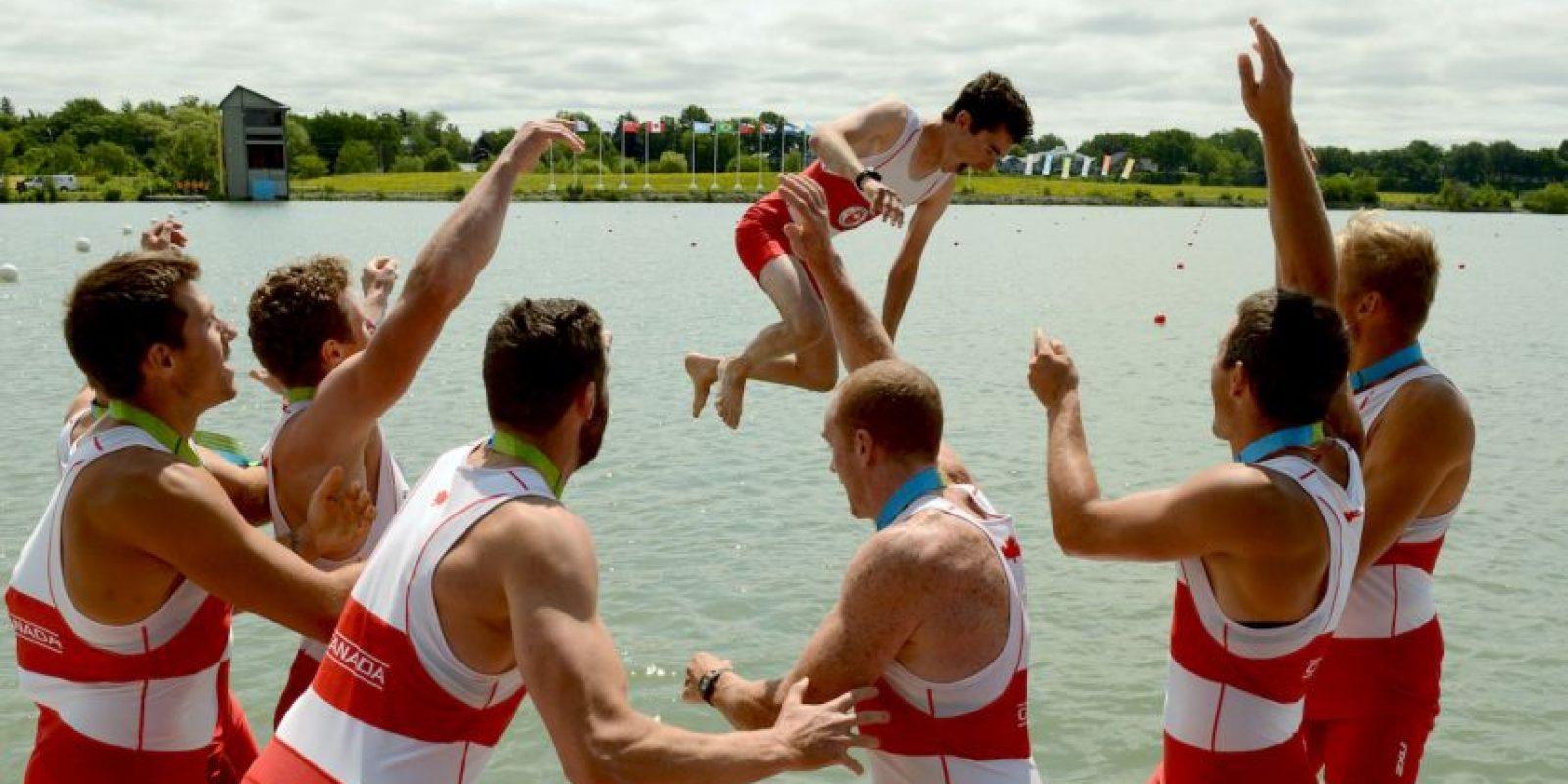 Miembros del equipo de remo de Canadá lanzan a uno de sus integrantes al agua. Foto:AFP