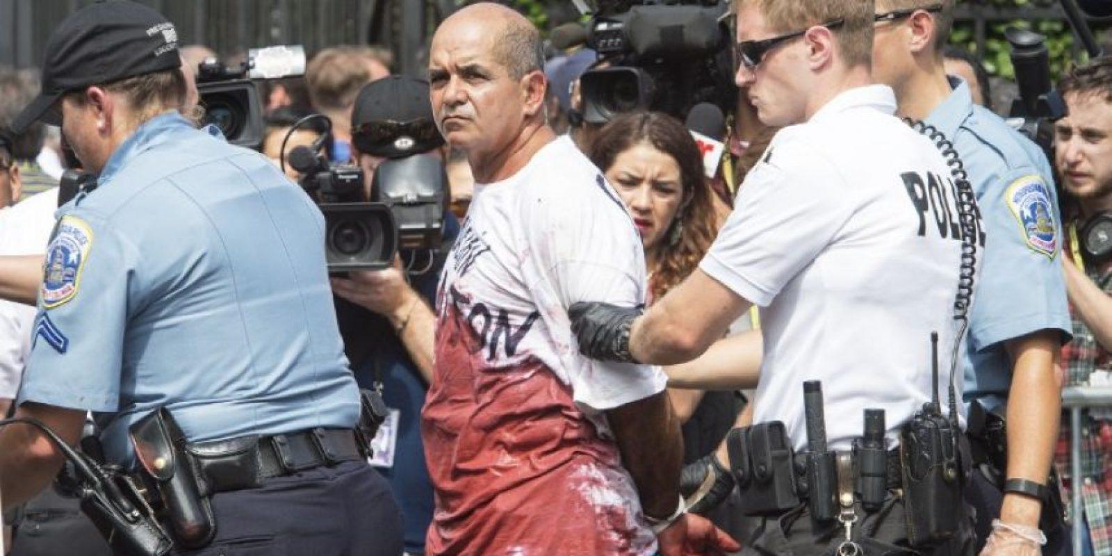 Un hombre fue detenido por manifestarse manchado de sangre falsa Foto:AFP