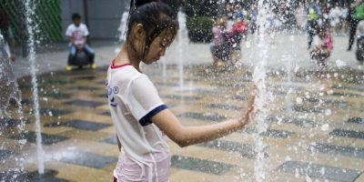 Niña se refersca del calor del verano en China. Foto: AFP