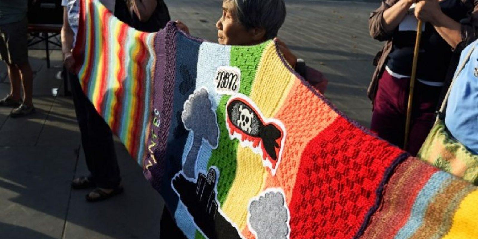 Francia: Una mujer que vivió en Osaka en 1945 sostiene una manta en protesta a la energía nuclear Foto:AFP