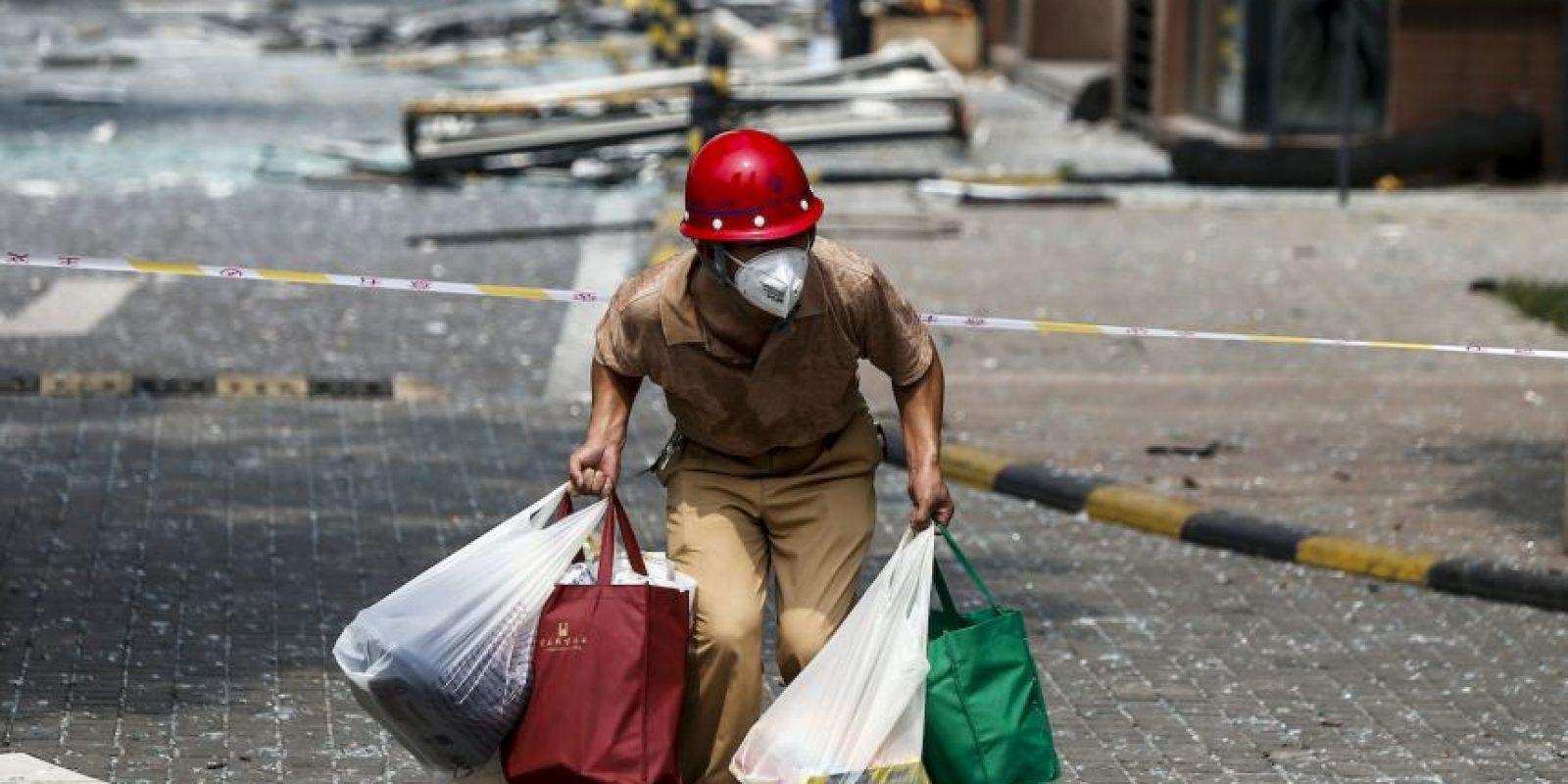Víctima de las explosiones en China carga sus pertenencias en busca de un lugar seguro. Foto:AFP