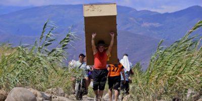 Colombianos deportados cargan sus pertenencias por el río Táchira. Foto:AFP