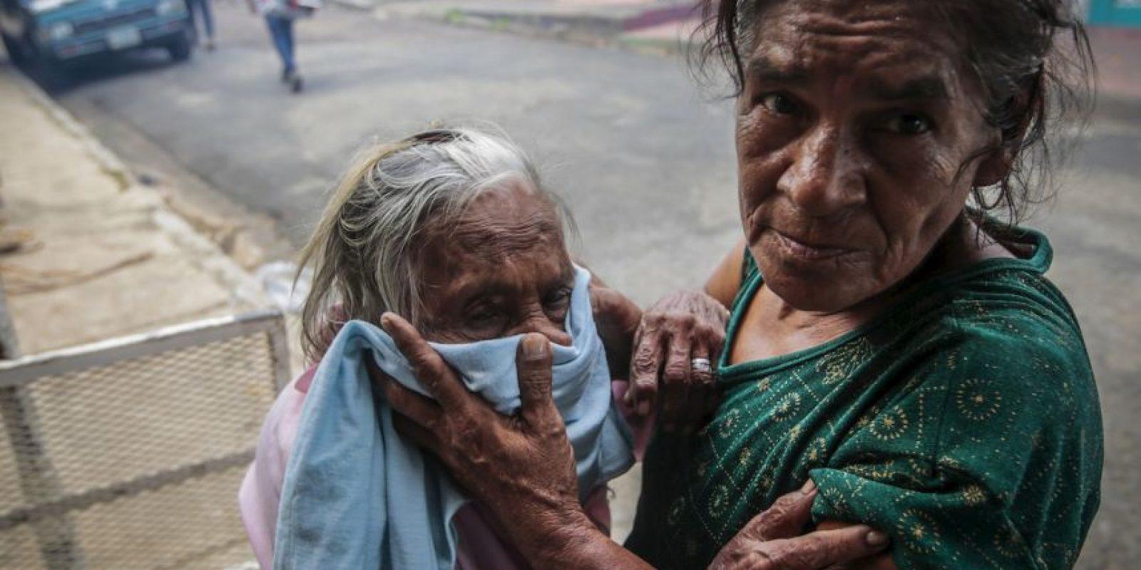 Una anciana es protegida mientras se fumiga contra el dengue en Nicaragua. Foto:AFP