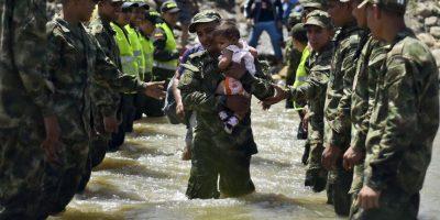 Bebé es cargado en el Río Táchira, entre la frontera de Venezuela y Colombia. Foto:AFP