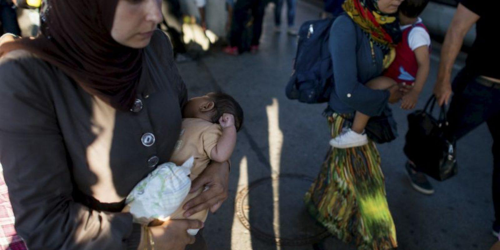 Mujeres cargan a sus hijos en estación del tren en Austria. Foto:AP
