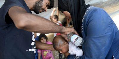 Migrantes refrescan a su bebé en la rentera de Macedonia y Grecia. Foto:AP