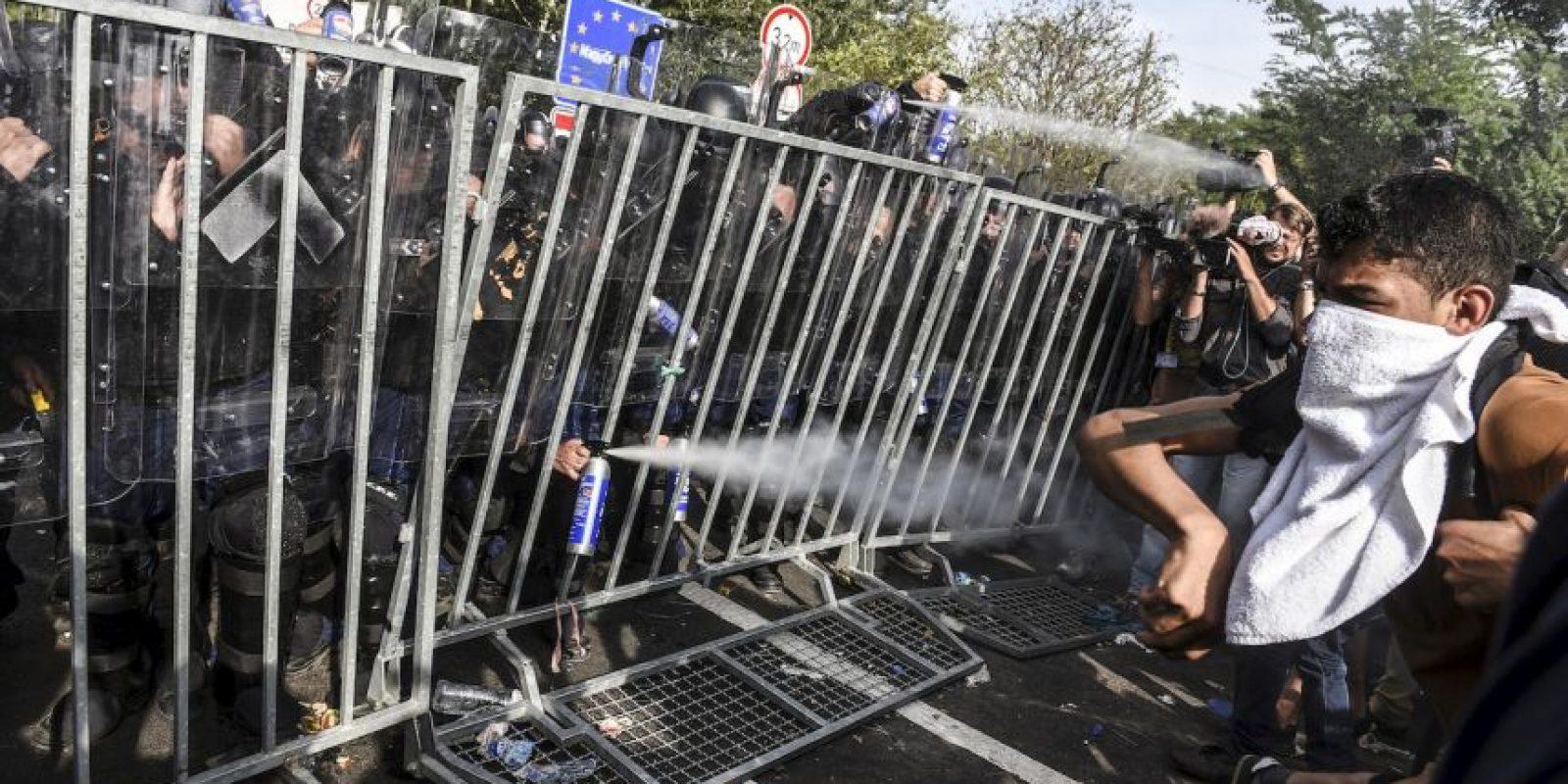 Policía antidisturbios de Hungría lanza gas pimienta a migrantes. Foto:AFP