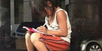 Niña haciendo su tarea en la calle conmueve Internet