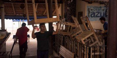 Los recidentes de las localidades resguardan sus negocios Foto:AP