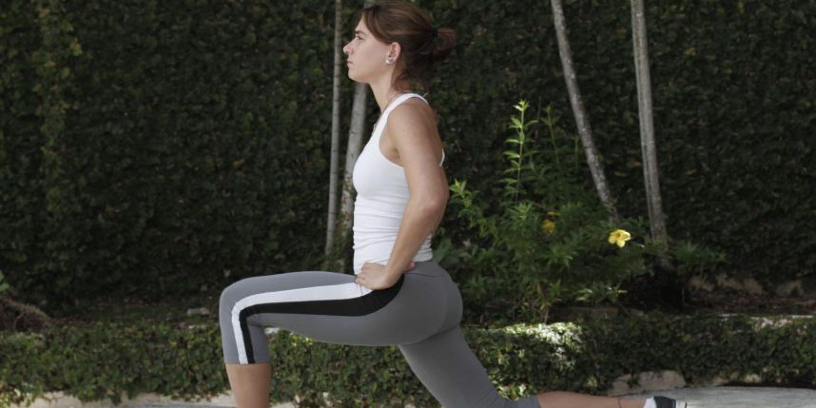 1Lunge Preparación: Separa las piernas al nivel de los hombros y coloca las manos en la cintura. Ejecución: Da un paso hacia adelante flexionando la rodilla hasta que la pierna de atrás casi toque el suelo.Incorpórate a la posición original y haz lo mismo con la otra pierna. Un consejo: No dejes que la rodilla de tu pierna delantera pase los dedos del pie. Mantén el pecho derecho, los abdominales contraídos y los hombros para atrás. Músculos a trabajar: Cuádriceps, gluteos, pantorrillas