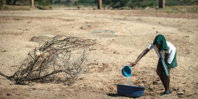 Una niña intenta recoger agua de un charco seco en Nongoma, Sudáfrica. Foto:AFP