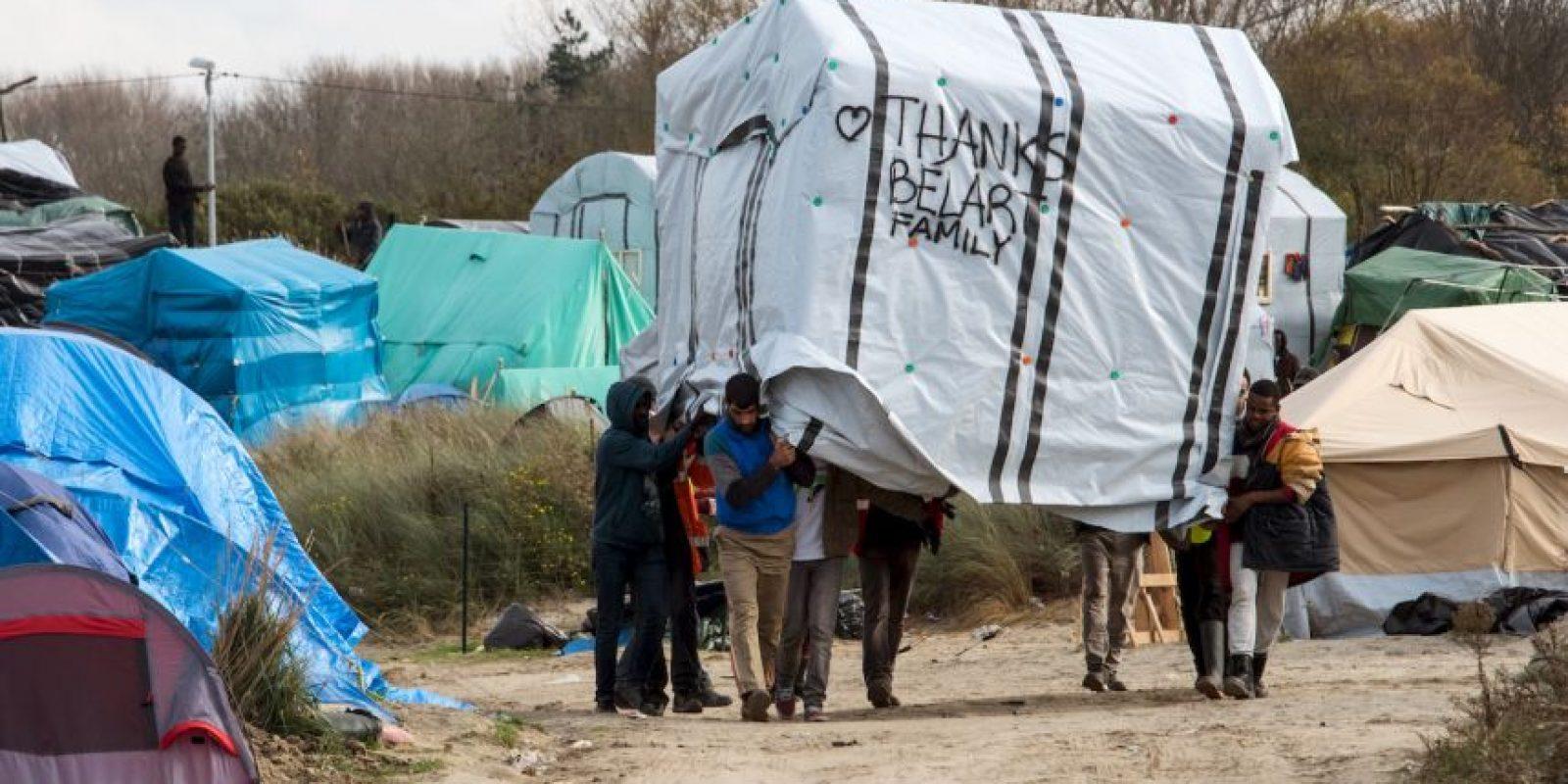 Migrantes mueven una tienda en Calais, Francia. Foto:AFP