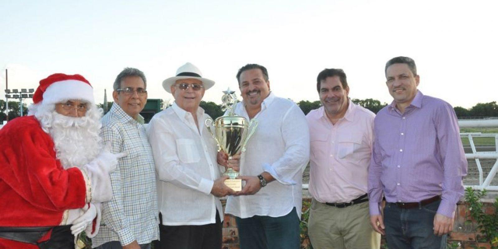 El doctor Angel Contreras hijo recibe de manos de Manfred Codik el trofeo correspondiente al campeón del Clásico Navidad 2015. Le acompaña el diputado Ricardo Contreras, entre otros. Foto:Fuente Externa