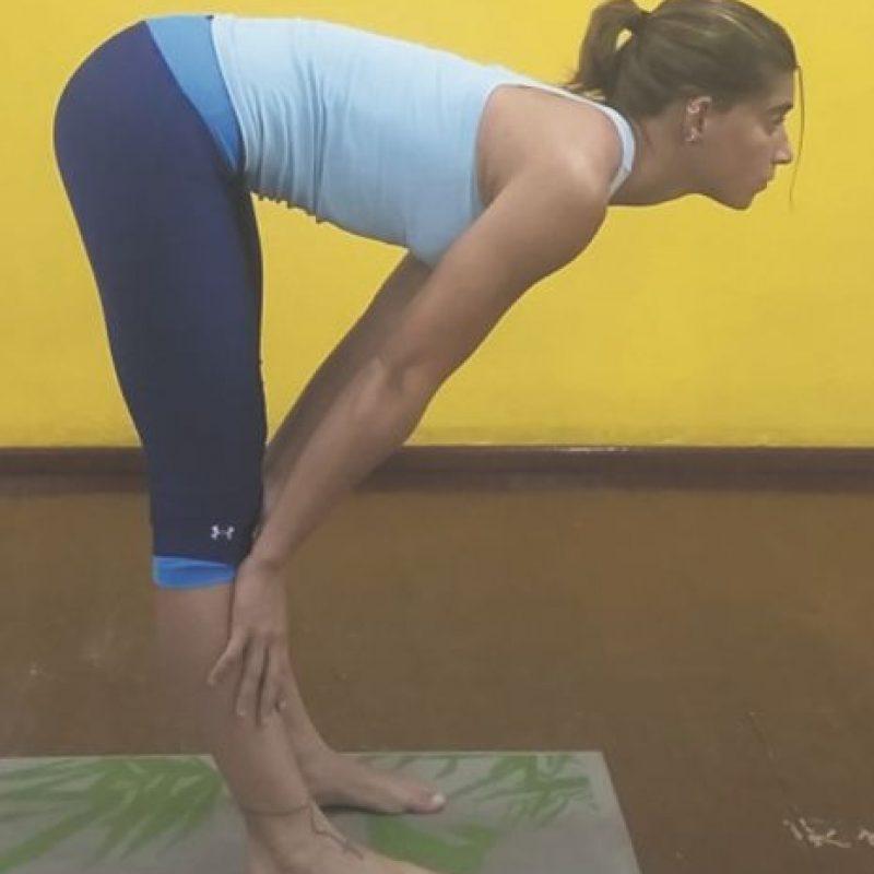 10 – Estiramiento femorales. Exhala y deja que el pecho vaya hacia tus rodillas manteniendo la espalda suave y relajada. Foto:Metro RD