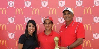 El presidente de la FEDOGOLF, Rafael Villalona, y Elybel Pimentel, cordinadora de mercadeo de McDonald's, premian a Enrique Valverde. Foto:Fuente Externa