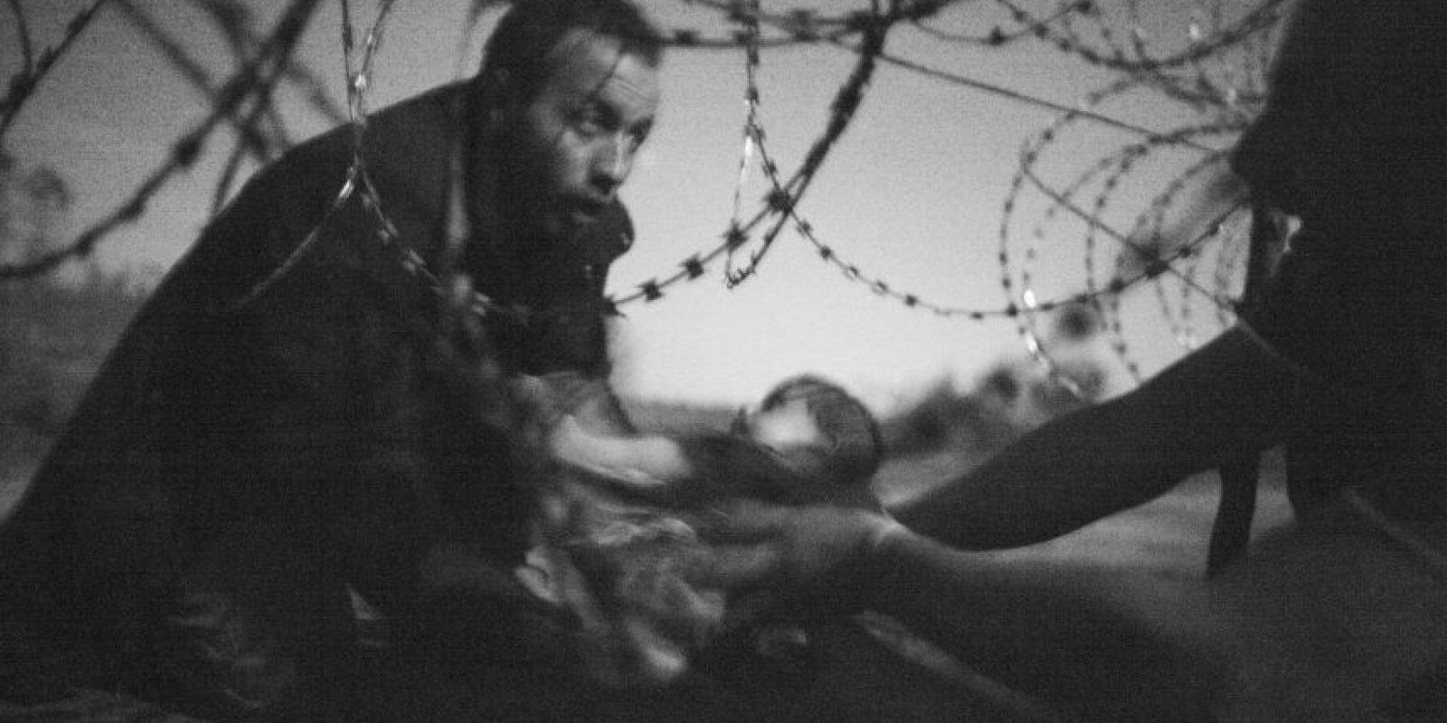 Foto del año. Tomada por Warren Richardson. Muestra a un hombre pasando a un bebé por una valla en construcción entre Serbia y Hungría Foto:worldpressphoto.org