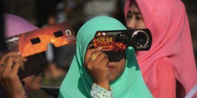 Los espectadores usan un filtro de luz solar hecho para poder apreciar el eclipse con seguridad. Foto:AFP