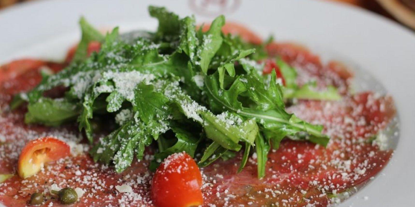 Carpaccio de res. Acompañado de rúcula fresca, tomaticos, alcaparritas y queso parmesano.