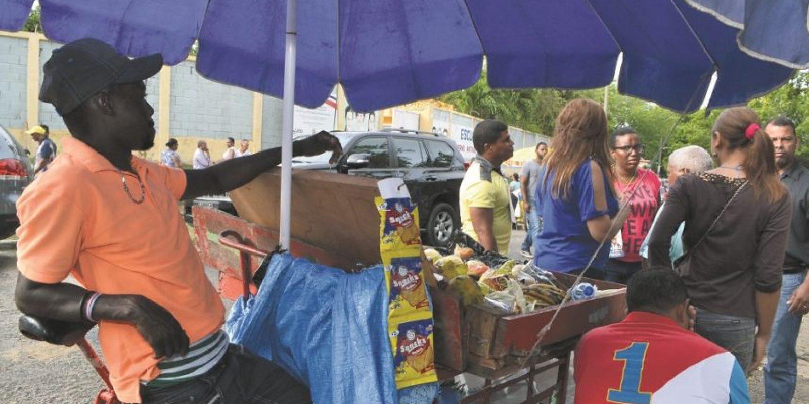 """15- La gente hizo su """"dinerito"""". El dominicano """"se la busca"""", y así quedó demostrado una vez más en este proceso electoral. Los vendedores ambulantes fueron protagonistas en los alrededores de los colegios y a ellos se sumó un nuevo personaje: la señora que por 25 pesos te cuidaba los celulares, sombrillas, carteras y monederos de los votantes que fueron con estos artículos prohibidos en las salas de votación. Foto:Fuente externa"""