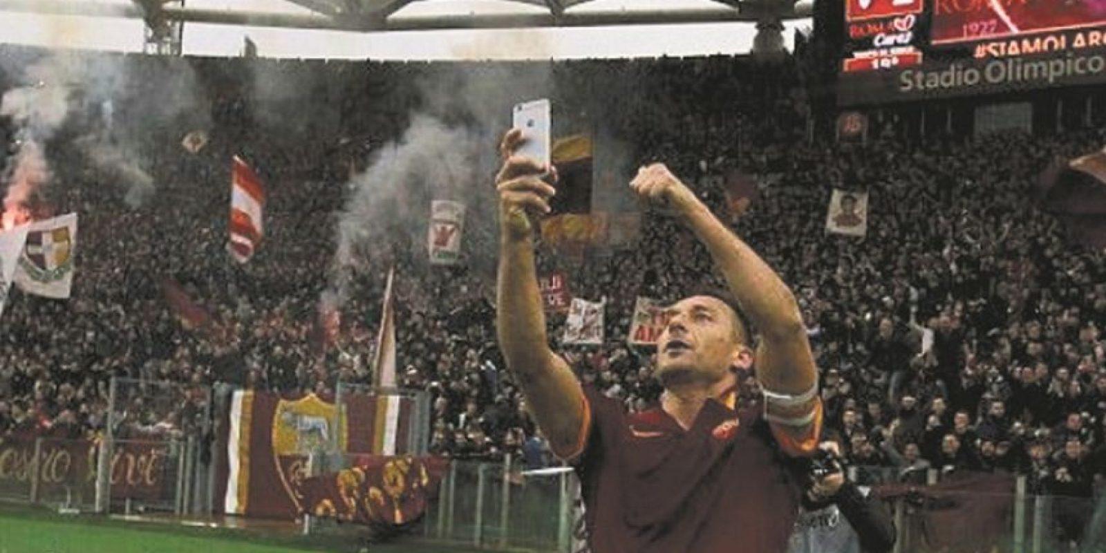 Totti con sus fanáticos. El 2015, Il Eterno Capitano anotó dos goles en el clásico ante Lazio y en el festejo del segundo tanto pidió prestado un dispositivo de telefonía móvil para retratar el momento junto a los tifosi de la Roma. Foto:Fuente externa