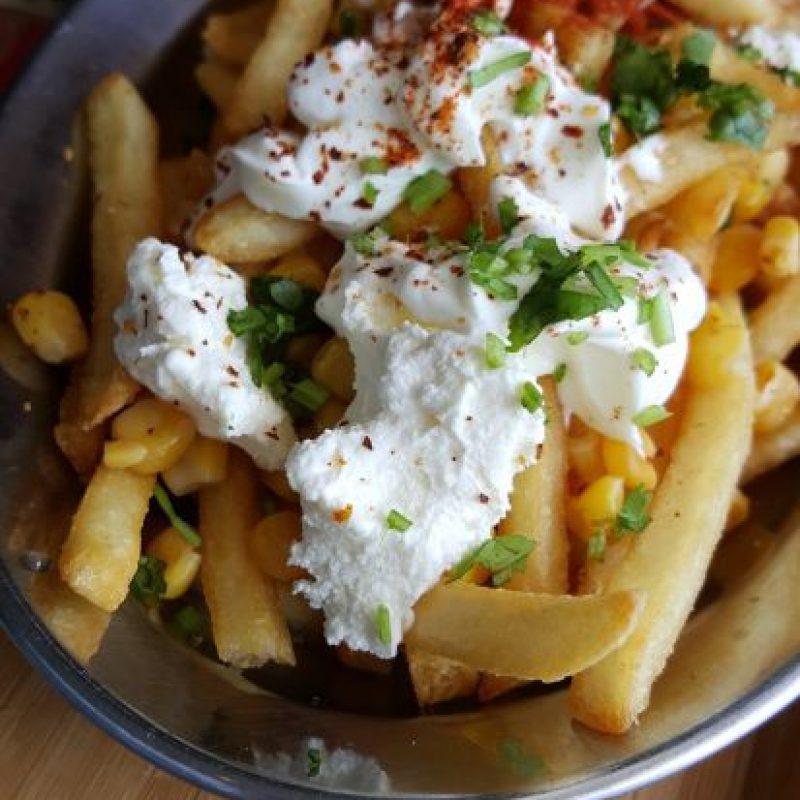 """¿Papas mexicanas? Se llaman """"Esquites Fries"""" y son una excelente opción para empezar tu visita por este restaurante. Combina papas fritas con maíz, queso blanco, limón, cilantro, chile y crema agria. Foto:Fuente externa"""