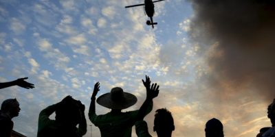 Residentes hacen señas a un helicóptero para que ayude a apagar incendio en Manila, Filipinas. Foto:AFP