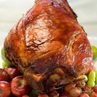 Pierna de cerdo glaseada al oporto. En República Dominicana no hay Navidad sin cerdo asado. Dale un toque diferente a este tradicional plato con la exquisita receta de Sagrario Matos.Ingredientes3 tazas de azúcar moreno, 4 tazas de jugo de piña, 1 cebolla blanca grande cortada en cuatro, 2 hojas de laurel, 2 astillas de canela, 1 botella de vino de oporto o vino moscatel, 1 pierna de cerdo ahumada de aproximadamente 18 libras.Preparación1. Precalienta el horno a 425º Fahrenheit (210º Celsius).2. Lleva al fuego el azúcar, el jugo de piña, el laurel, la canela y el vino de oporto. Remueve hasta que el azúcar se disuelva y deja hervir removiendo hasta que reduzca un poco.3. Elimina la grasa extra de la pierna y marca la grasa grande del lomo. Vierte la salsa reducida sobre la pierna de cerdo (con el lado de la grasa para abajo) y cubre la pata con papel de aluminio. 4. Hornea por aproximadamente una hora. Destapa y mantente bañándola con su jugo y la salsa de piña y oporto mientras permanece en el horno una hora más (voltea y cocina con la parte de la piel hacia arriba). Saca del horno y deja refrescar. Decora con frutas y sirve junto a la salsa de oporto.Ingredientes salsa de oporto.5 clavos de olor, 5 granos de pimienta enteros, 1 cda de maicena diluida en 1 taza de jugo de piña, 2 tazas de vino de oporto.Preparación de la salsa Reduce a fuego medio todos los ingredientes moviendo regularmente. Foto:Marjorie Torres