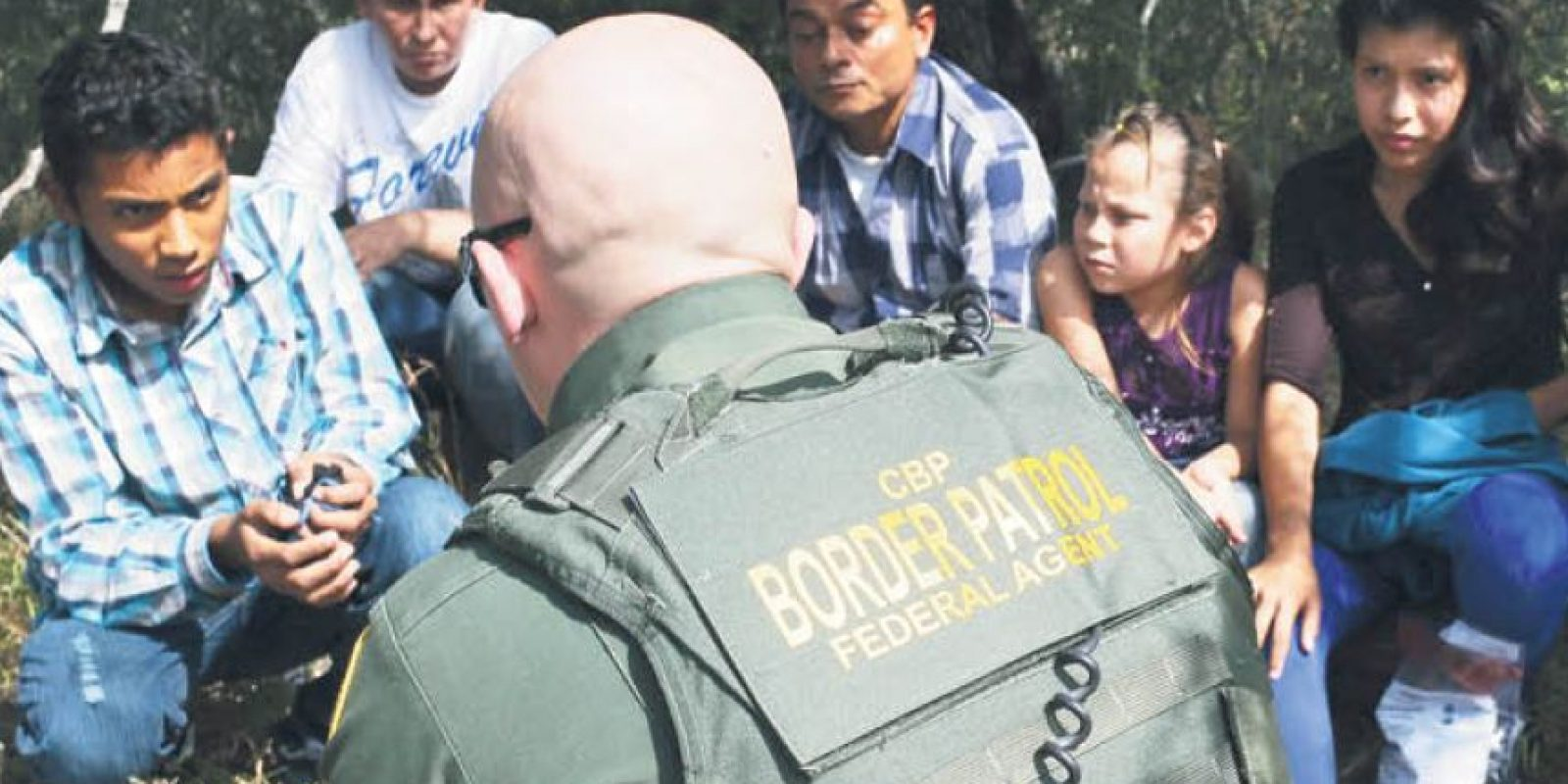 Un agente fronterizo entrevista a migrantes en la frontera México – EEUU. Foto: Getty Images