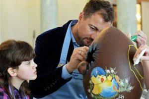 Polonia. El ex miembro del Real Madrid, Jerzy Dudek, junto a una niña decoran un tradicional huevo de chocolate en convención