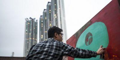 Hong Kong: Un artista pinta un grafitti sobre una réplica del Muro de Berlín. Foto:AFP