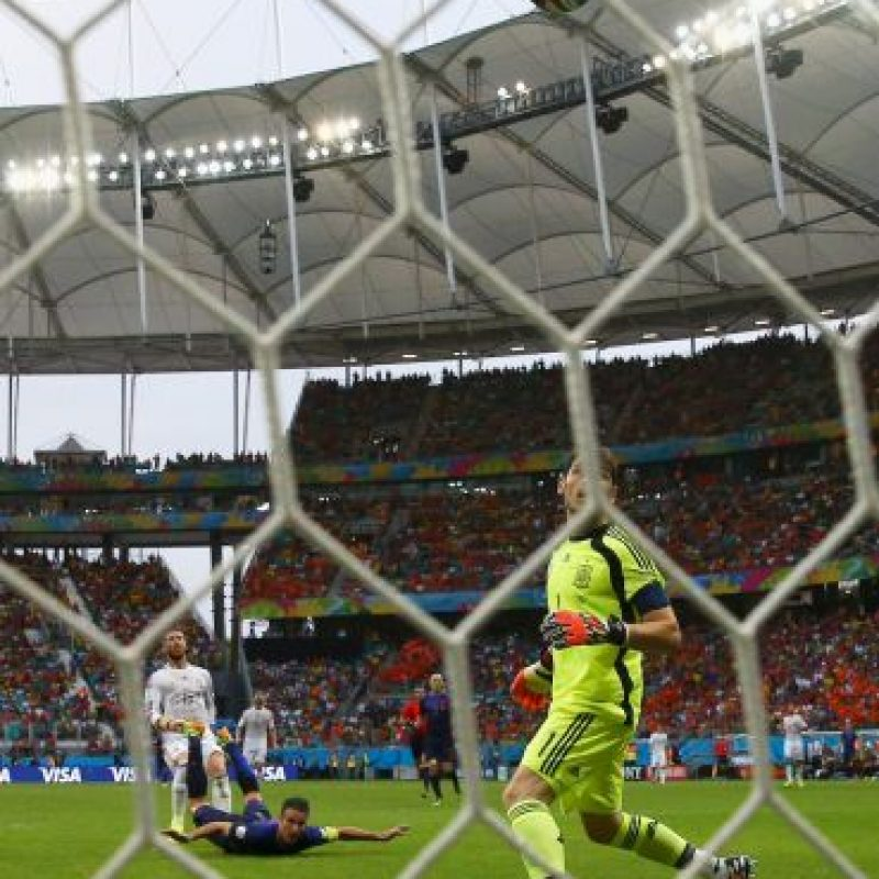 Van Persie mirando en el suelo, Casillas pegado al piso sigue con la vista el balón Foto:Getty Images