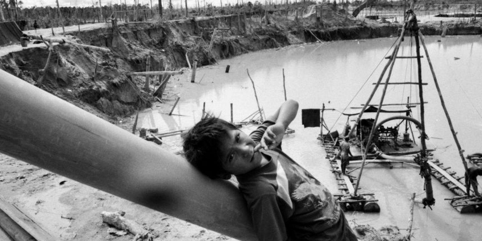 """En esta foto tomada el 28 de mayo 2014, un niño se apoya en un tubo que es parte de un surtidor hidráulico conocido localmente como """"chupadera"""", en un improvisado campamento minero en La Pampa, en la región Madre de Dios, Perú. La minería ilegal de oro no es la mayor amenaza para la selva de Perú. Eso viene de la agricultura a pequeña escala por inmigrantes pobres de las tierras altas del país andino, dijo el ministro del Ambiente, Manuel Pulgar-Vidal. La tala y las plantaciones ilegales de aceite de palma también representan un problema para la selva. La toxicidad del mercurio ha contaminado la cadena alimentaria, incluidos los peces, principal fuente de proteínas de la población local. El país pierde cientos de millas cuadradas de un año debido a la deforestación. Foto:AP Photo/ Rodrigo Abd"""