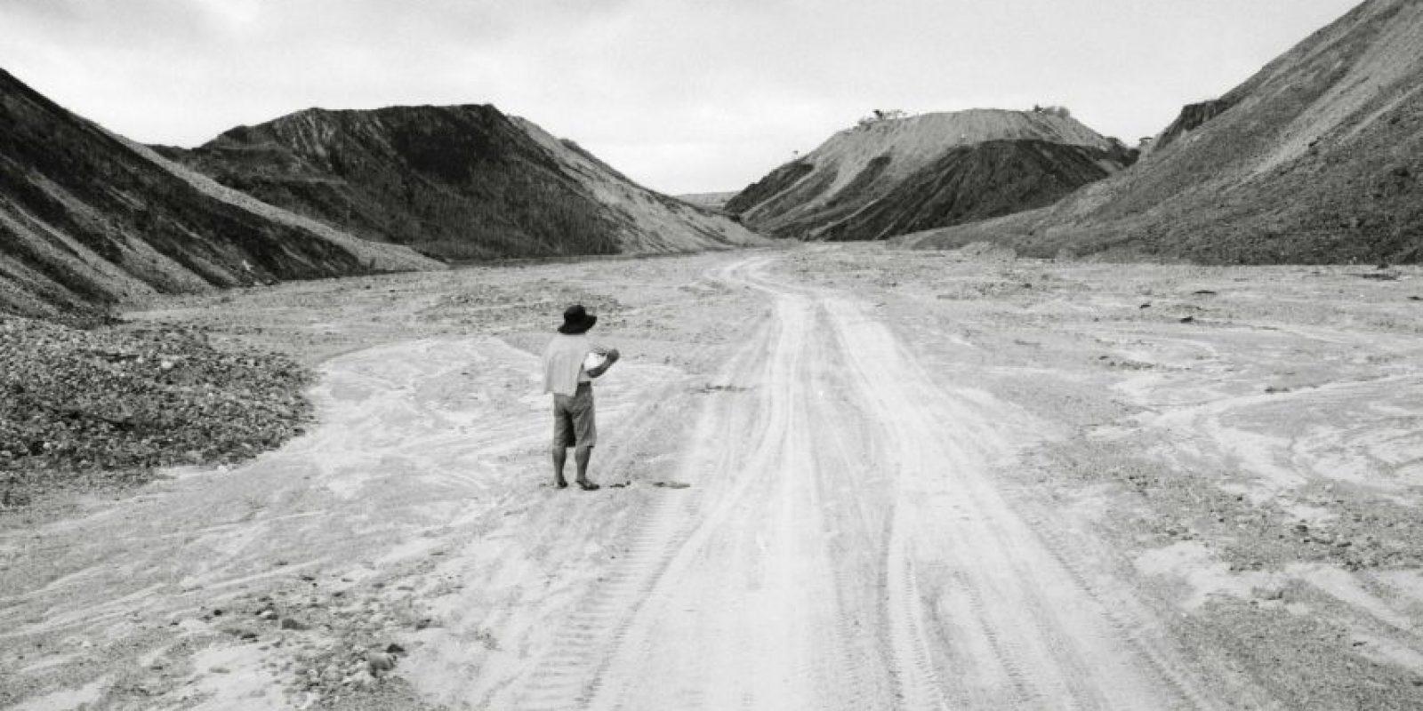 Un minero espera en la carretera debido al denso tráfico que se generó antes de la llegada de la policía para resolver la minería ilegal en Huepetuhe, en la región de Madre de Dios, Perú. El país andino criminalizó la minería de oro sin licencia en 2012, aun que la ley entró en vigor este año una vez se empezaron a utilizar explosivos para la extracción. Dichas operaciones han desplazado a miles de mineros, de las aproximadamente 40.000 personas que según las autoridades se trasladaron a la selva para extraer oro. 22 de mayo, 2014. Foto:AP Photo/ Rodrigo Abd