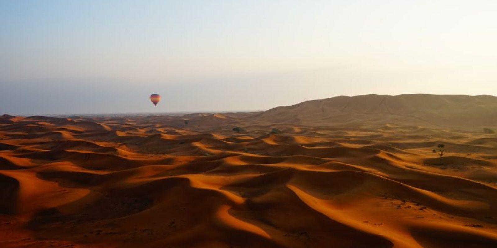 La captura, tomada alrededor de unos 30 minutos después de la salida del sol, muestra un globo aerostático en la distancia cuando comienza a descender sobre una granja de camellos. La imagen se hizo desde otro globo, sobre las dunas. Foto:Agencias