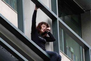 Una empleada del gobierno en Grecia intentando saltar de la ventana de su oficina luego de ser despedida. Foto:Agencias