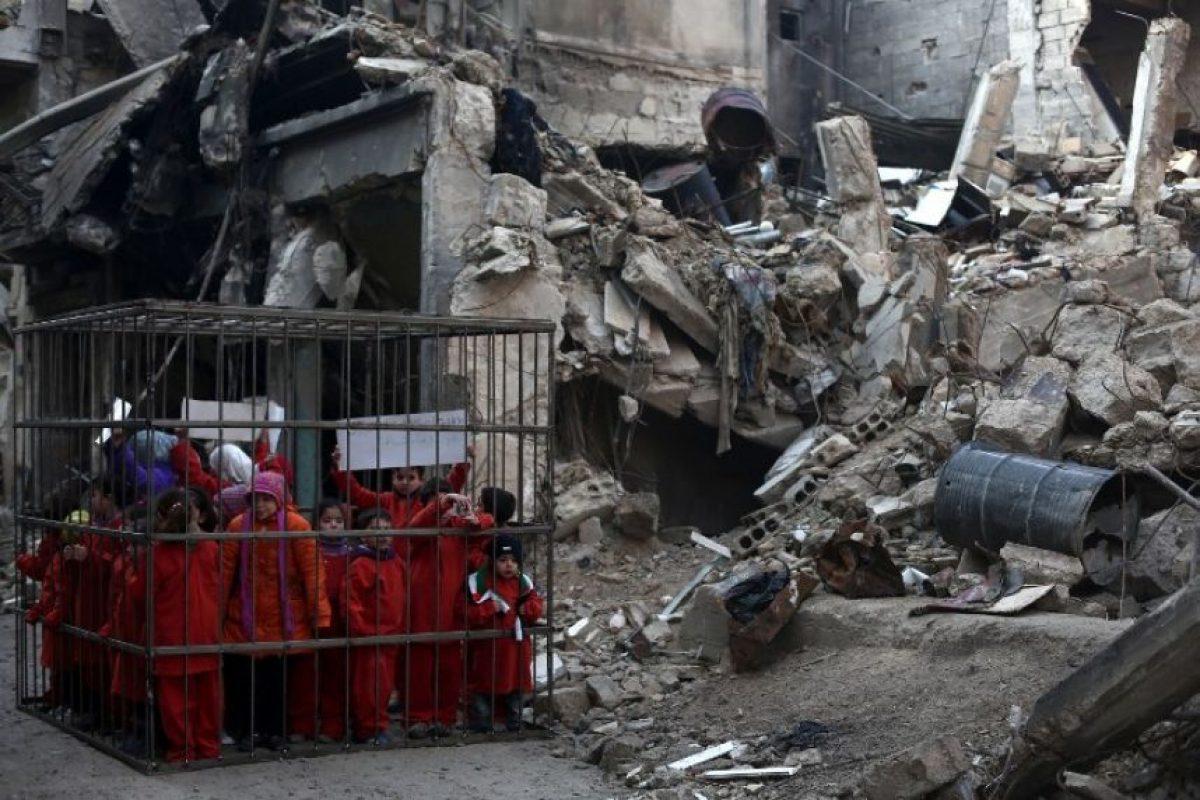 Una organización denunció las matanzas de niños encerrando a menores en una jaula y simulando que los quemaba vivos Foto:AFP