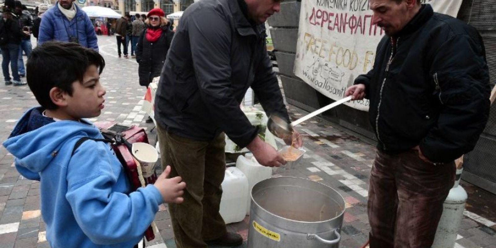 Personas reciben comida gratis en los comedores comunitarios Foto:AFP