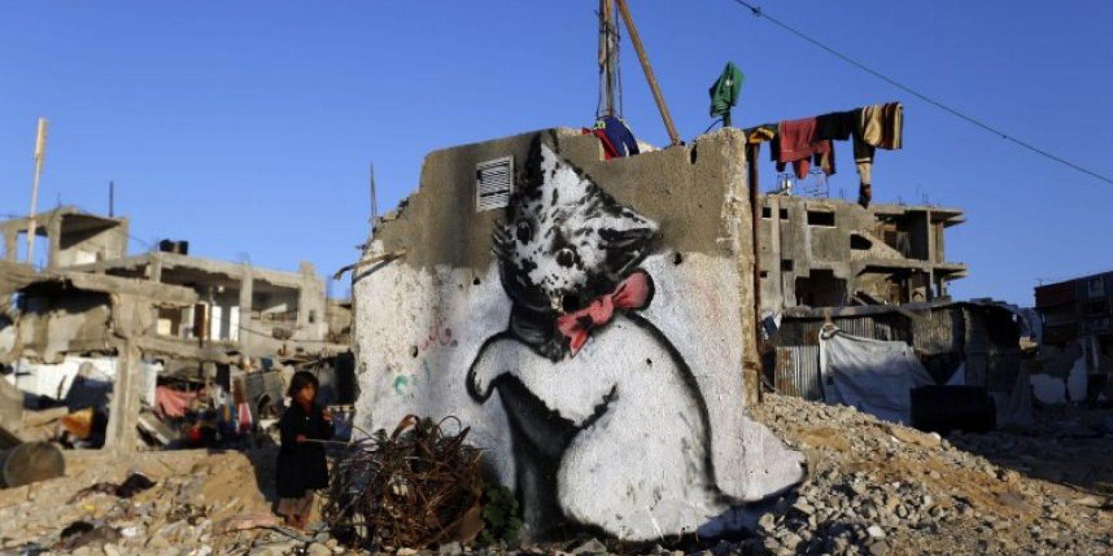 Un niño se para junto a un mural pintado por el artista británico Banksy, en las ruinas de la Franja de Gaza Foto:AFP