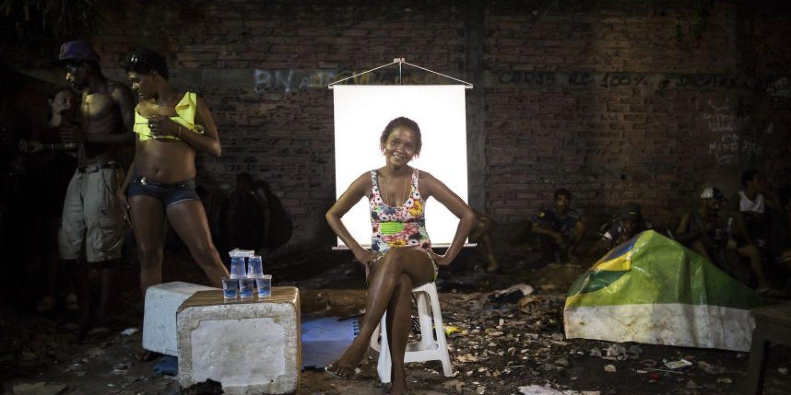 """En esta imagen, tomada el 18 de marzo de 2015, Carla Cristina, de 26 años, posa para una fotografía junto a su puesto de venta de agua en un punto de venta de crack al aire libre, conocido como """"cracolandia"""", donde los clientes pueden comprar la droga y fumarla a plena vista, de día o de noche, en Río de Janeiro, Brasil. Foto:AP/ Felipe Dana"""