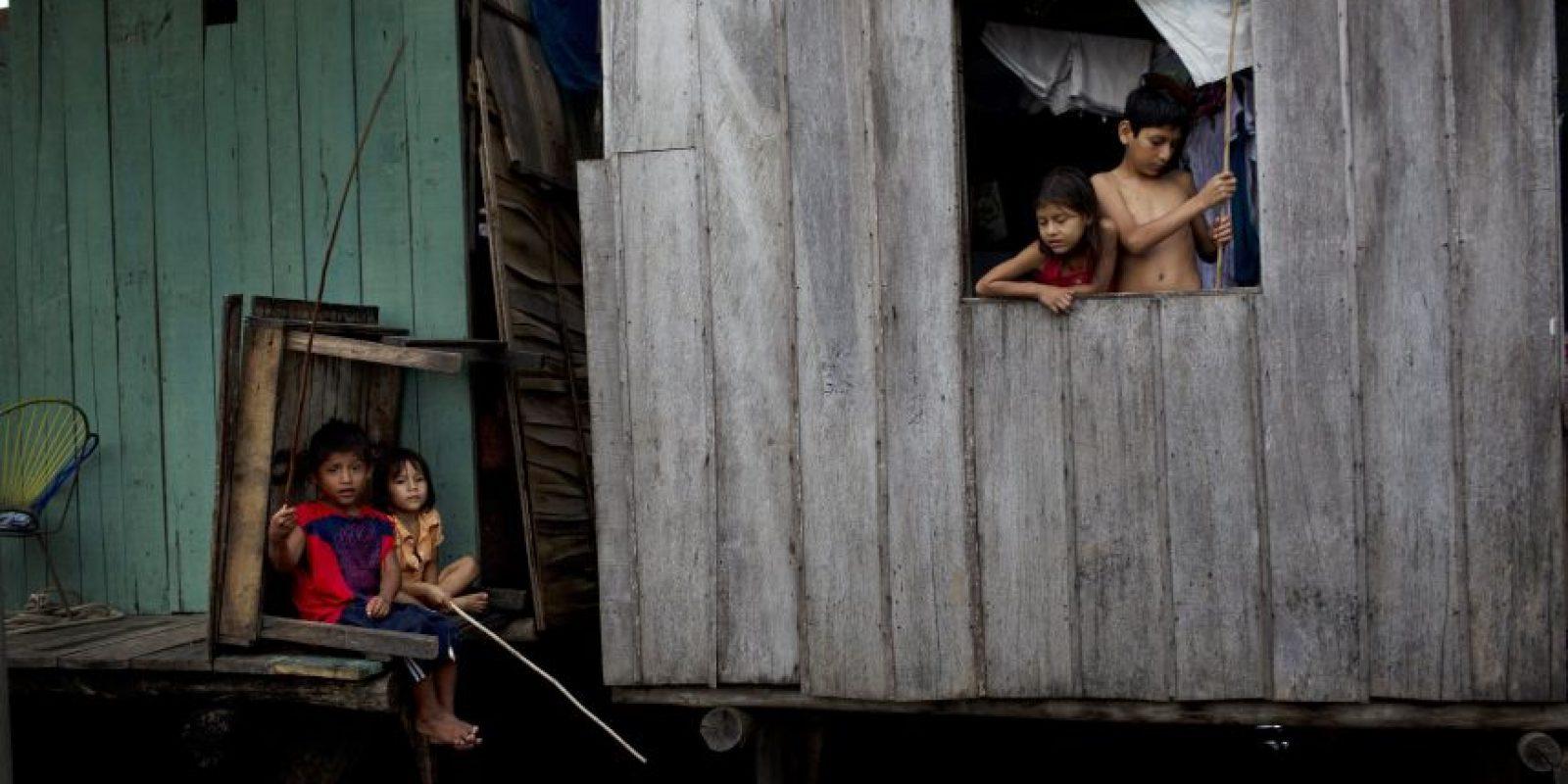 """En esta imagen del 19 de abril de 2015, niños pescanod desde sus casas, justo por encima del nivel del agua enBelén, una empobrecida comunidad peruana conocida como """"Venecia de la jungla"""" en Iquitos, Perú. Además de las casas, la comunidad cuenta con una iglesia católica y vairas evangélicas. También tiene burdeles, discotecas aserraderos y casinos. Foto:AP/ Rodrigo Abd"""