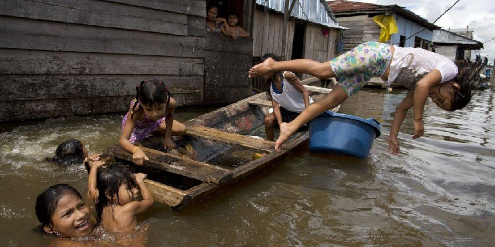 """En esta imagen del 19 de abril de 2015, niños jugando en un bote en el agua ante sus casas en el barrio de Belén en Iquitos, Perú. Esta empobrecida comunidad peruana conocida como """"Venecia de la jungla"""", vive la mitad del año inundada, con canoas en lugar de taxis motocicleta como medio de transporte preferido. Foto:AP/ Rodrigo Abd"""
