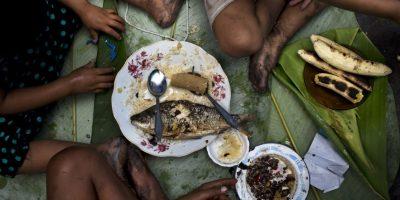 """En esta omagen del 20 de abril de 2015, los hermanos Piero, Ariana y Priscila comen pescado, bananas y arroz mientras sus padres venden pescado en un mercado en el barrio de Belén en Iquitos, Perú. Esta empobrecida comunidad peruana conocida como """"Venecia de la jungla"""". Según estadísticas oficiales, el 40% de los niños en Belén sufren malnutrición y el 66% de la población es pobre. Foto:AP/ Rodrigo Abd"""