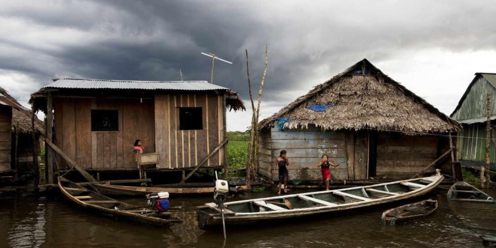 """En esta imagen de 19 de abril 2005, embarcaciones amarradas a casas en una tarde lluviosa een el barrio de Belén en Iquitos, Perú. Esta empobrecida comunidad peruana conocida como """"Venecia de la jungla"""", vive la mitad del año inundada, con canoas en lugar de taxis motocicleta como medio de transporte preferido. Para que la viviendas no se inunden cuando el río ITaya se desborda, se construyen tres metros por encima del suelo, sostenidas por postes, de madera de la jungla. Foto:AP/ Rodrigo Abd"""